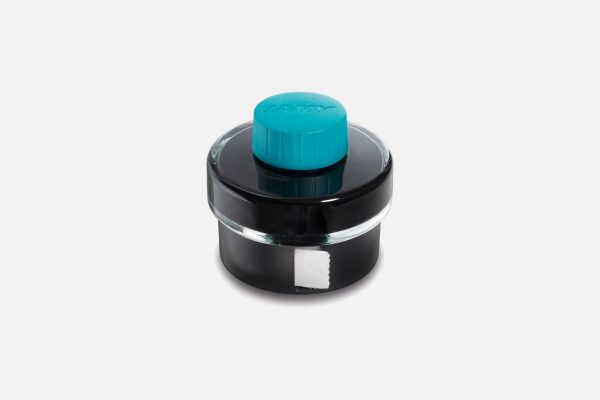 a 50ml glass bottle of lamy t 52 turquoise ink and built in blotting paper roll on a grey background